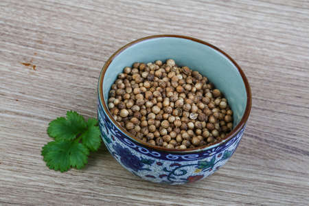 coriander seeds: Coriander seeds with leaves on the wood background