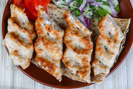 kebob: Chicken kebab with onion rings, tomato and salad leaves Stock Photo