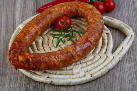 krakow sausage: Sausage ring with cherry tomato and rosemary on the wood background
