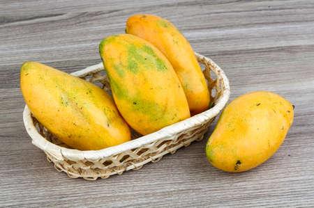 mango fruta: Mango amarillo maduro en la cesta sobre fondo de madera Foto de archivo