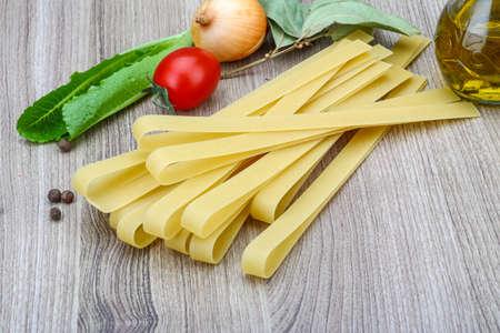fettuccine: Italian raw Pata Fettuccine on the wood background