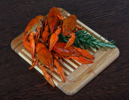 lobster dinner: Boiled Crayfish with rosemary on the wood background