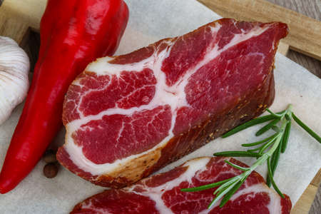 chuck: Chuck steak with rosemary, pepper and garlik on wood background