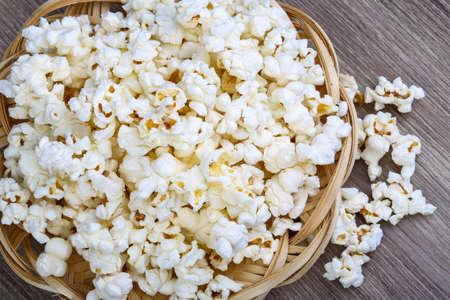 popcorn bowl: Fresh hot Popcorn in the basket on wood background