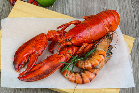 lobster isolated: Big cooked lobster and tiger shrimps ready for eating Stock Photo