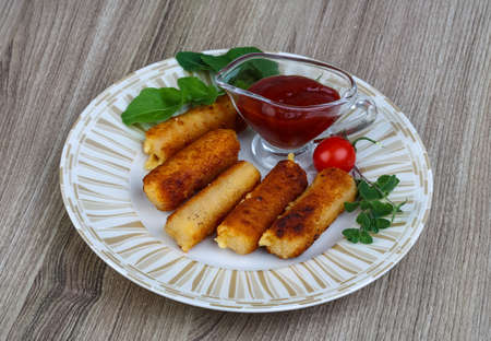 crust crusty: Fried Cheese sticks with sauce and rucola leaves Stock Photo