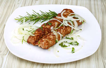kabab: Kebab barbecue with rosemary and onion rings on the wood background Stock Photo