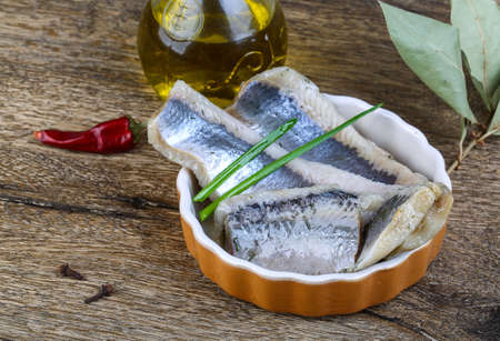 seafish: Herring fillet with dill, oil and spices on the wood background Stock Photo