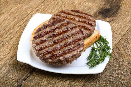 グリル ハンバーガー カツレツ牛肉ひき肉ウッドの背景に
