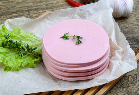 bologna baloney: Sliced sausages with salad leaves and thyme on the wood background Stock Photo