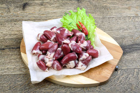 innards: Raw chicken hearts ready for cooking on the wood background