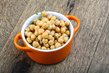 vegetable tin: Canned chickpeas in the bowl on wood background
