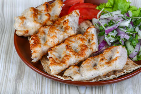 kebab: Chicken kebab with onion rings, tomato and salad leaves Stock Photo
