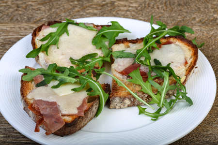 ruccola: Bruchetta with prosciutto, parmesan and fresh ruccola Stock Photo