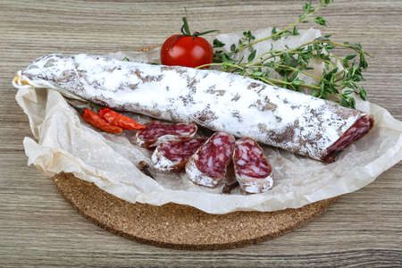 embutido: Traditional Spanish sausages- fuet with thyme leaves on the wood background Stock Photo