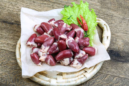 fat bird: Raw chicken hearts ready for cooking on the wood background