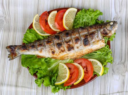 Grilled trout barbeque served lemon, tomato and salad leaves Standard-Bild