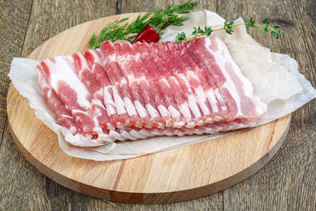 raw bacon: Raw sliced bacon ready for cooking on wood background Stock Photo