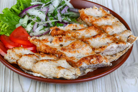 kabab: Chicken kebab with onion rings, tomato and salad leaves Stock Photo