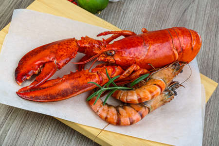 raw lobster: Big cooked lobster and tiger shrimps ready for eating Stock Photo