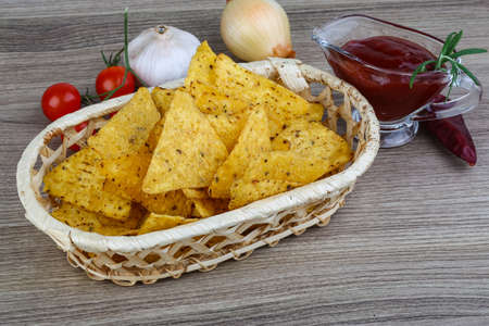 nachos: Nachos chips with tomato hot sauce on the wood background Stock Photo