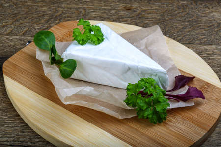 brie: Soft brie cheese served parsley leaves on wooden background Stock Photo