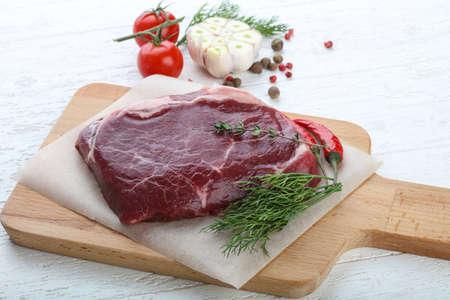 ribeye: Raw ribeye steak with thyme and dill on wood background