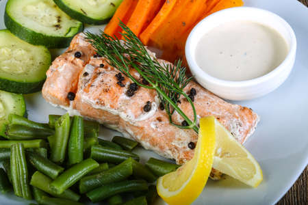 dinner food: Baked salmon with vegetables and white sauce