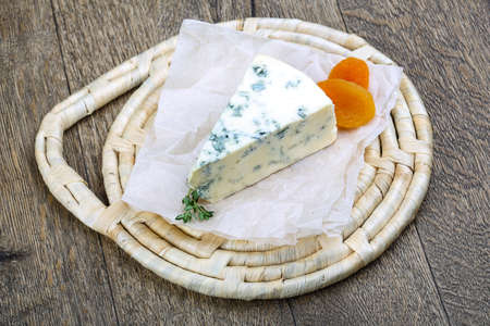 roquefort: Roquefort cheese with thyme and dry apricot on the wood background