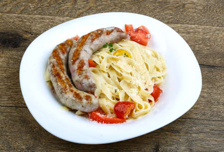 sizzle: Grilled sausages with pasta on the wood background