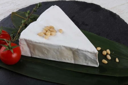 brie: Brie cheese on bamboo leaves with cedar nuts Stock Photo