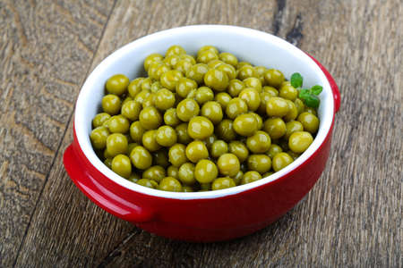 vegetable tin: Canned green peas in the bowl on wood background