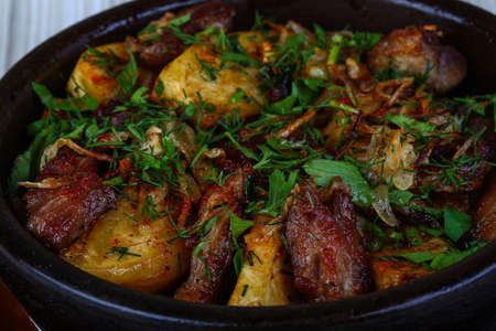 Baked potato with pork meat served fresh herbs
