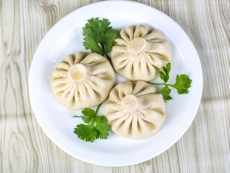 Caucasuan cuisine - Khinkali with meat served green koriander leaves