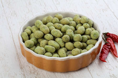 wasabi: Wasabi peas in the bowl on wood background