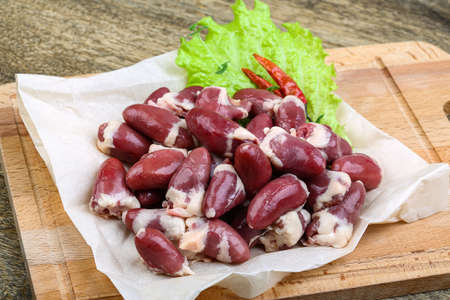 giblets: Raw chicken hearts ready for cooking on the wood background