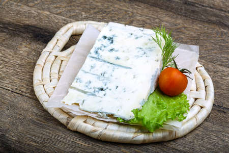 gorgonzola: Gorgonzola cheese in wood background with salad leaves and tomato