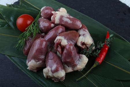 giblets: Raw chicken hearts with pepper and thyme on the bamboo leaves