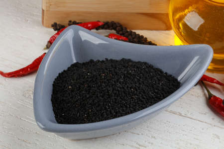 nigella seeds: Dry nigella in the bowl on wood background