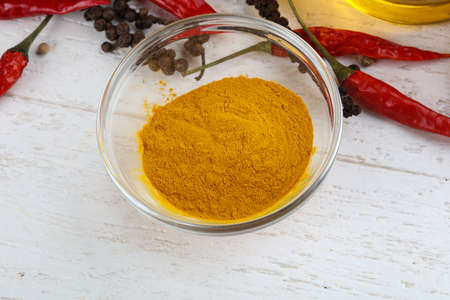 curcuma: Curcuma powder in the bowl on wood background Stock Photo