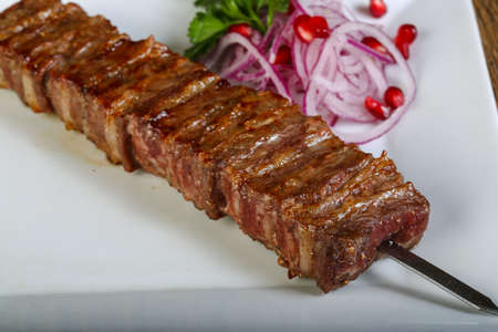 bbq grill: Grilled bbq ribs with onion, parsley and pomegranet seeds Stock Photo