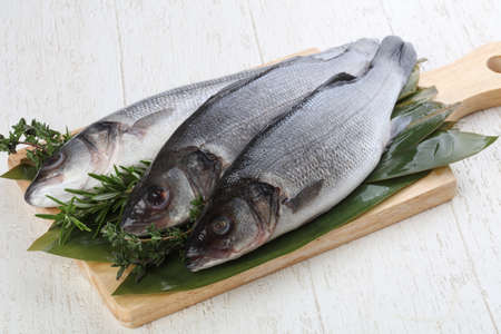 whitefish: Raw seabass fish with thyme and rosemary Stock Photo