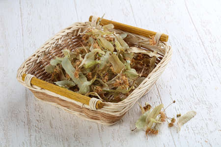 linden flowers: Dry linden flowers in the basket on wood background
