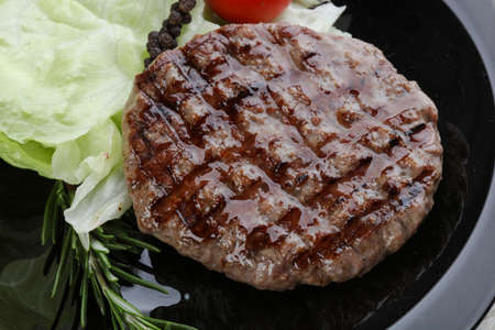 fast food restaurant: Grilled burger cutlet with rosemary and salad leaves Stock Photo