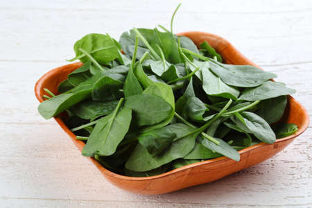 spinach: Hojas de espinaca en la canasta en el fondo de madera