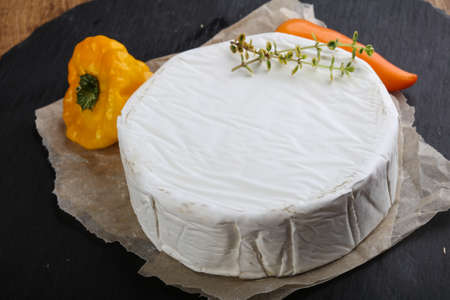 camembert: Camembert cheese with thyme on wood background Stock Photo