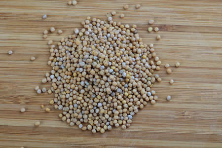 indian mustard: Mustard seeds - spice for cooking on the wood background Stock Photo