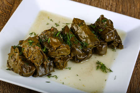 food backgrounds: Dolma - stuffed meat in grape leaves with sauce