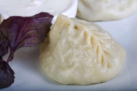 uzbek: Uzbek dumplings with sauce and basil leaves