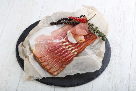 jamon: Sliced jamon with thyme on wood background